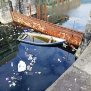 old half sunken row boat surrounded by rubbish in a canal